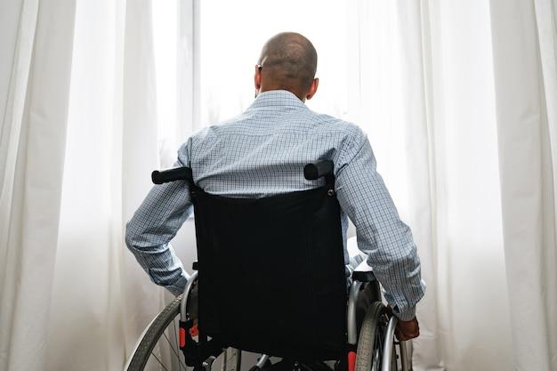 Афро-американский мужчина в инвалидной коляске сидит у окна один дома