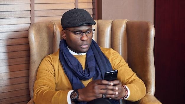 アフリカ系アメリカ人の男は彼の手にスマートフォンを持つカフェの椅子に座っています。