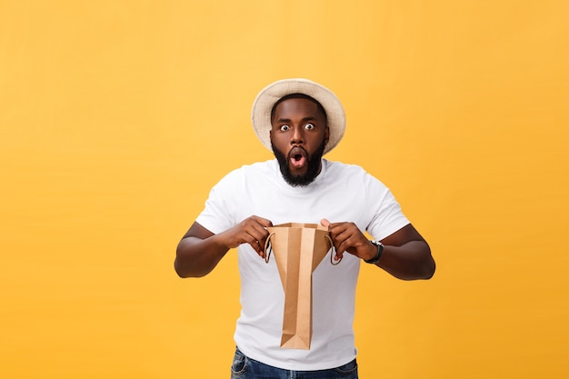 African american man is surprised opning a paper bags