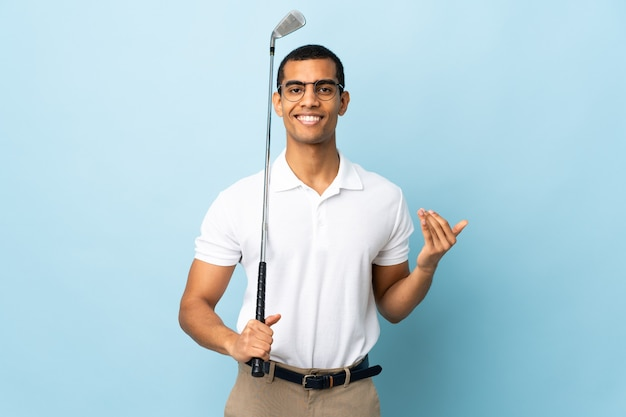 African american man over isolated blue background playing golf and doing coming gesture