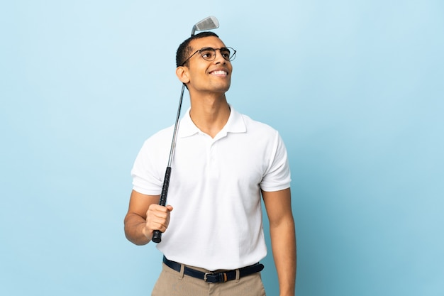 African american man over isolated blue background playing golf and looking up while smiling