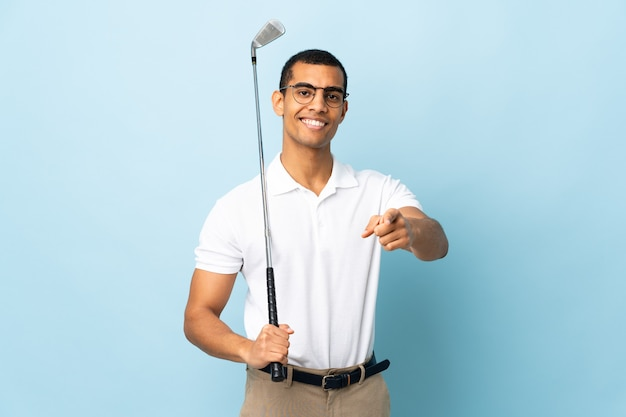 African american man over isolated blue background playing golf and pointing to the front