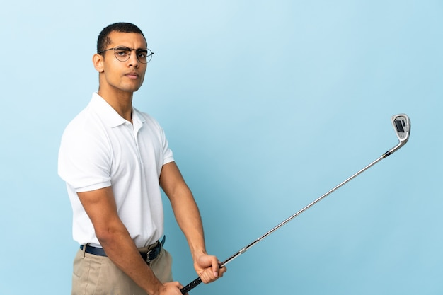 African american man over isolated blue background playing golf