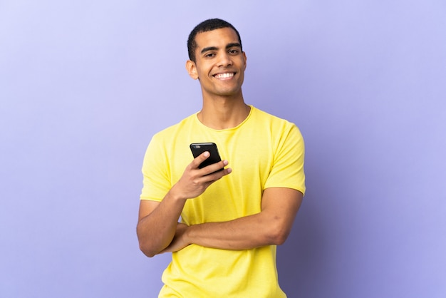 African american man over isolated purple wall using mobile phone laughing