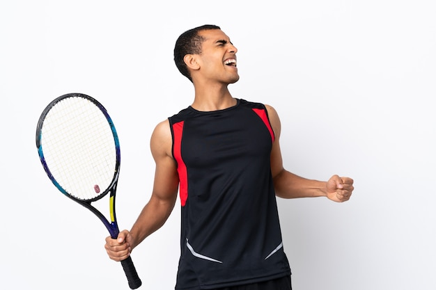 African american man over isolated white background playing tennis and celebrating a victory