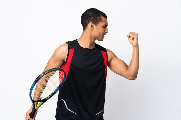 African american man over isolated white wall playing tennis and celebrating a victory