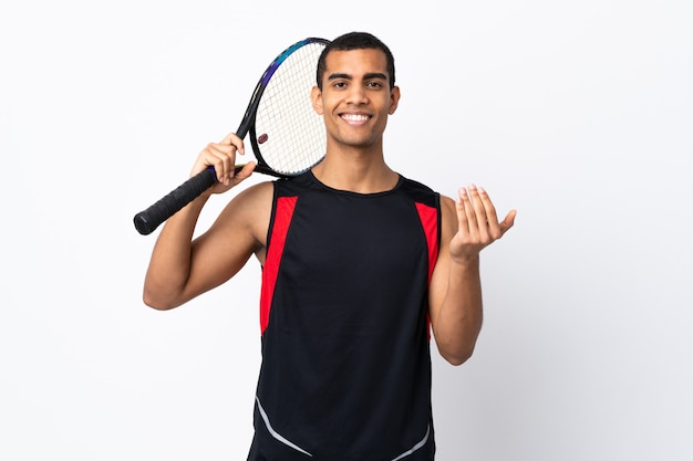 African american man over isolated white wall playing tennis and doing coming gesture