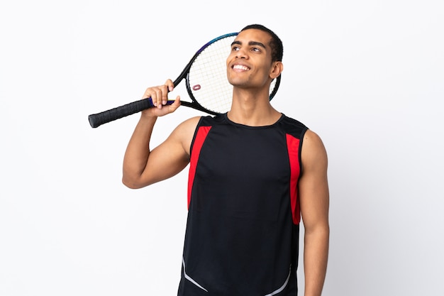 African american man over isolated white wall playing tennis and looking up