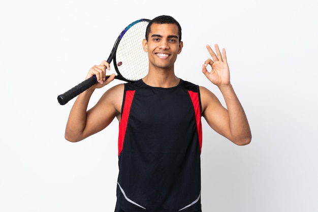 African american man over isolated white wall playing tennis and making ok sign