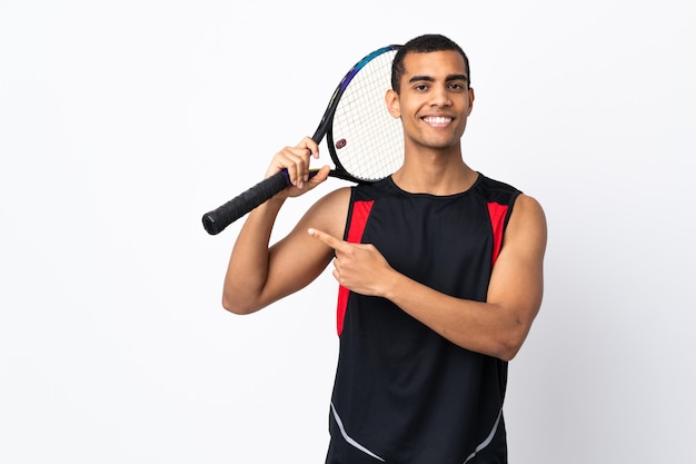 African american man over isolated white wall playing tennis and pointing to the lateral