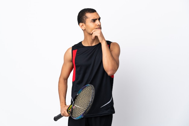African american man over isolated white wall playing tennis and thinking