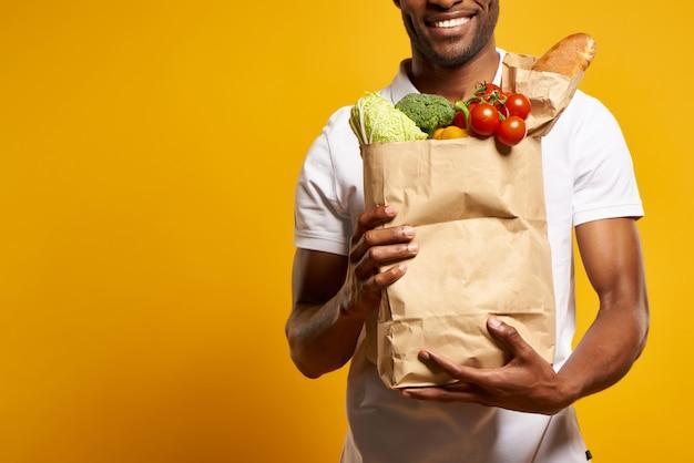 Афро-американский мужчина держит бумажный мешок со свежими продуктами.