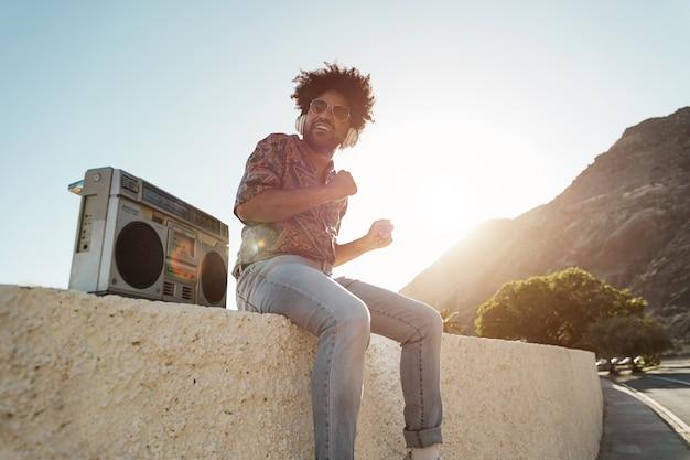 ビーチで屋外のビンテージラジカセステレオで音楽を聴くアフリカ系アメリカ人の男-顔に焦点を当てる