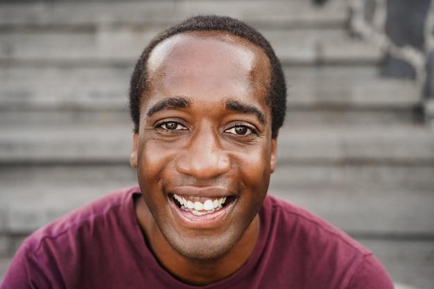 도시에서 야외 카메라를 보고 있는 아프리카계 미국인 남자 - 얼굴에 초점