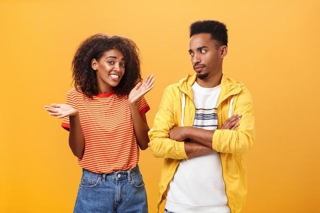 Афро-американский мужчина смотрит на девушку, скрестив руки на груди, пока она извиняется, пожимая плечами через оранжевую стену