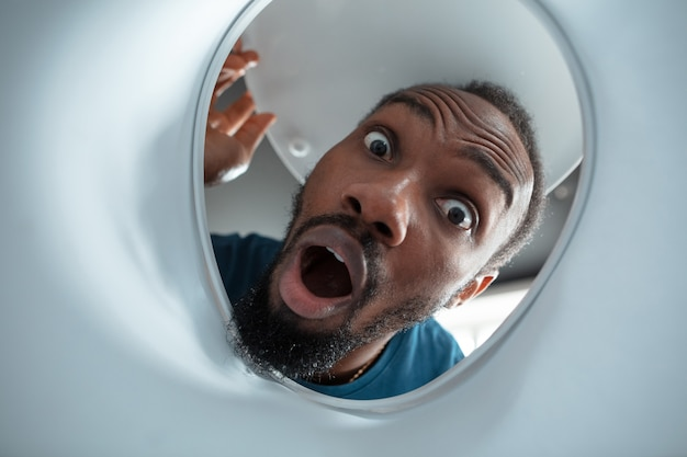 African-american man looking for something in unusual places at his home