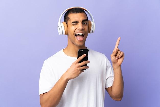 Афро-американский мужчина на изолированном фиолетовом слушает музыку с мобильным телефоном и поет
