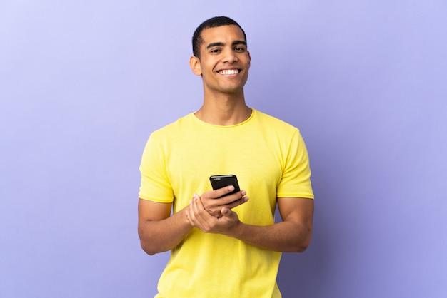 Афро-американский мужчина на изолированном фиолетовом с помощью мобильного телефона аплодирует
