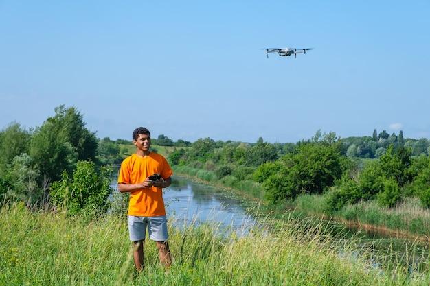 초원에 손에 컨트롤러와 함께 무인 항공기를 운영 하는 아프리카 계 미국인 남자