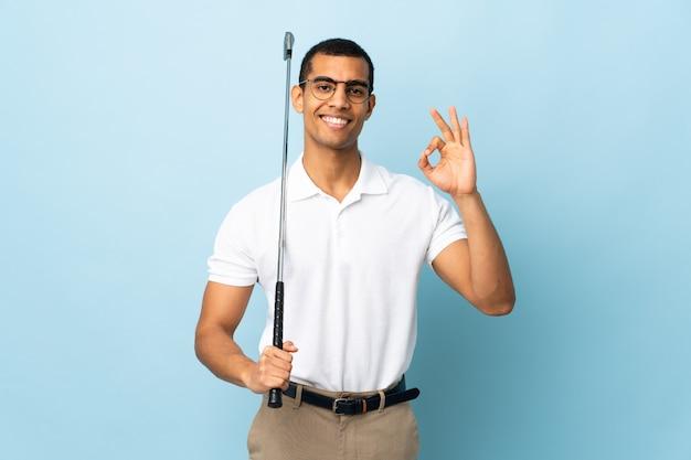 골프 확인 표시를 만드는 고립 된 파란색 벽에 아프리카 계 미국인 남자