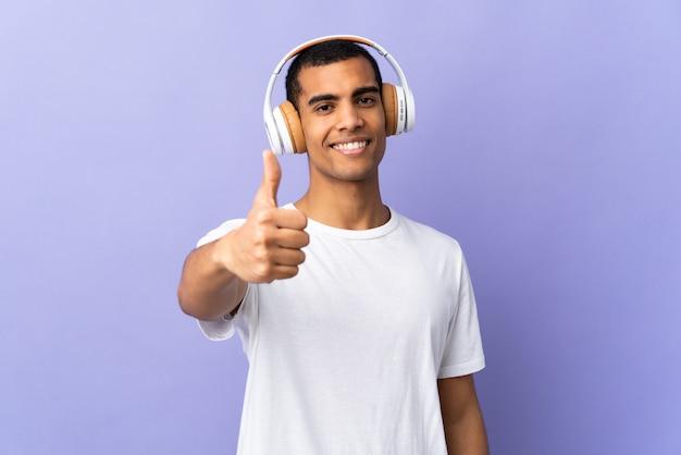 Афро-американский мужчина над изолированной пурпурной стены прослушивания музыки и с пальца вверх