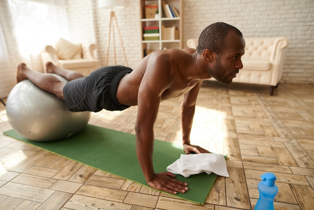 African american man performs plank at home.