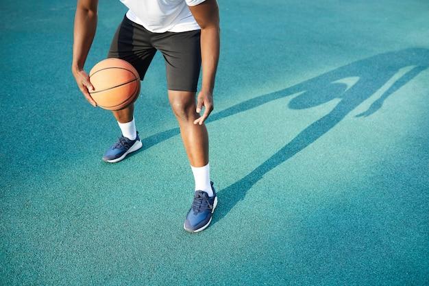 アフリカ系アメリカ人の男がバスケットボールをプレー