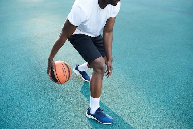 アフリカ系アメリカ人の男がバスケットボールのクローズアップを再生