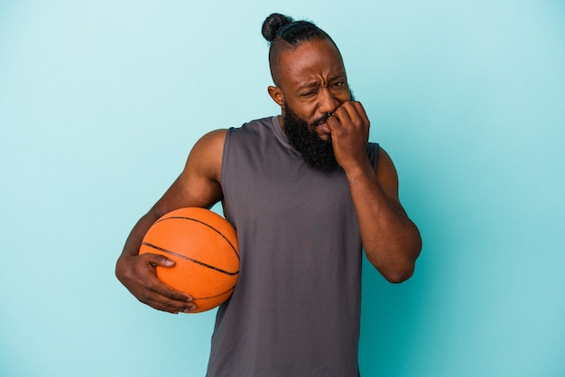 神経質で非常に不安な、青い背景の爪を噛んで孤立したバスケットボールをしているアフリカ系アメリカ人の男。