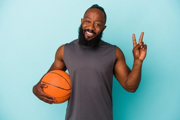 파란색 배경에 격리된 농구를 하는 아프리카계 미국인 남자는 손가락으로 평화 상징을 보여주는 즐겁고 평온합니다.