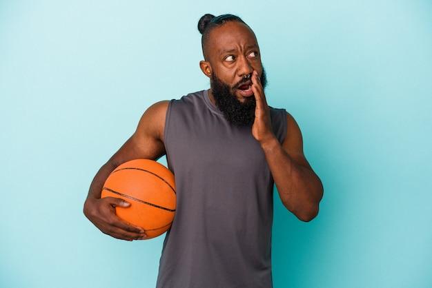 파란색 벽에 고립 된 농구를하는 아프리카 계 미국인 남자는 비밀 뜨거운 제동 뉴스를 말하고 옆으로보고있다