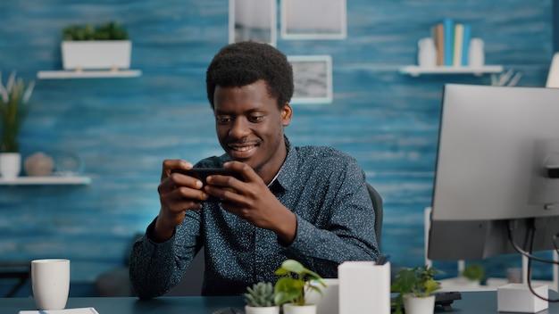 彼の携帯電話でビデオゲームをしているアフリカ系アメリカ人の男