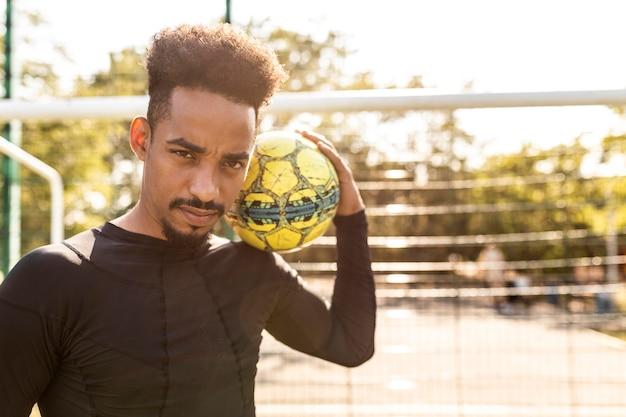 Афро-американский мужчина играет с футбольным мячом на открытом воздухе