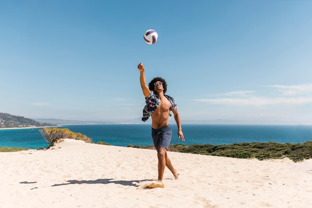 African american man playing with ball on beach