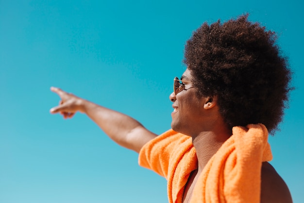 African american man pointing away against sky