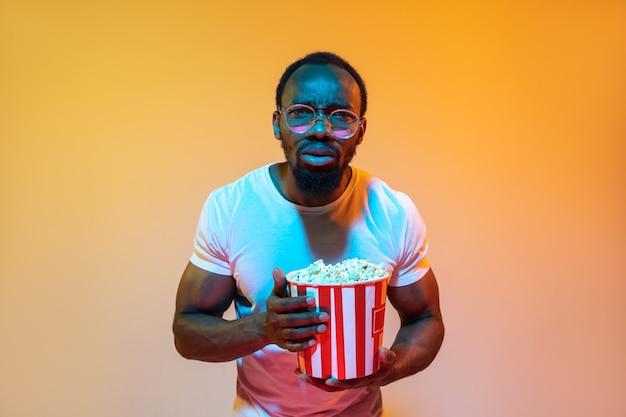 African american man portrait isolated on gradient orange in neon light