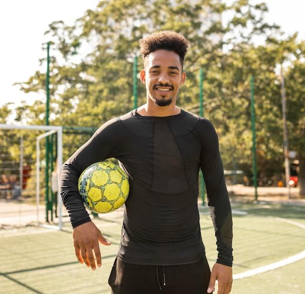 サッカーでポーズをとるアフリカ系アメリカ人の男