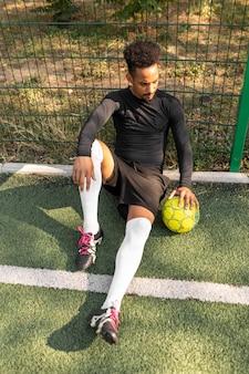 外でサッカーボールでポーズをとるアフリカ系アメリカ人の男