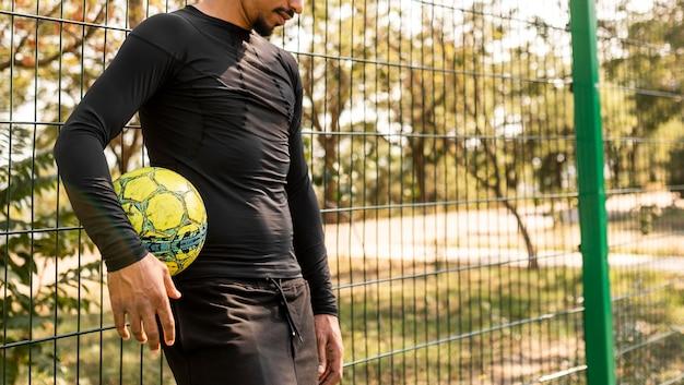 Афро-американский мужчина позирует с футбольным мячом с копией пространства