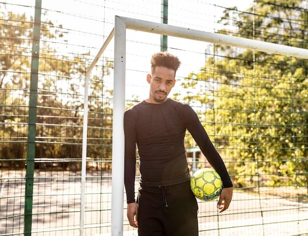 Афро-американский мужчина позирует с футбольным мячом