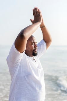 African american man practicing yoga at the beach