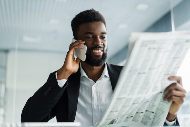 African american man reading newspaper and talking on phone in office