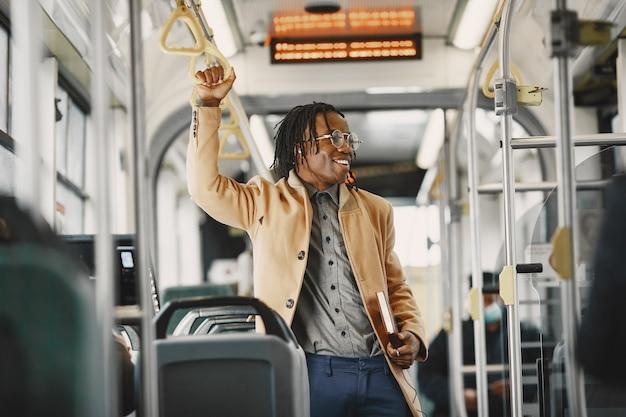 Uomo afroamericano che guida nel bus della città. ragazzo con un cappotto marrone. uomo con il taccuino.