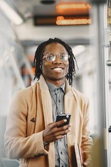 Uomo afroamericano che guida nel bus della città. ragazzo con un cappotto marrone.