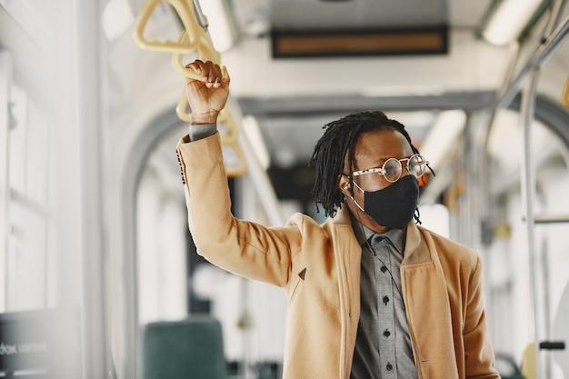 도시 버스를 타고 아프리카 계 미국인 남자입니다. 갈색 코트를 입은 남자. 코로나 바이러스 개념.