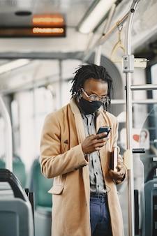 도시 버스를 타고 아프리카 계 미국인 남자입니다. 갈색 코트를 입은 남자. 코로나 바이러스 개념. 무료 사진