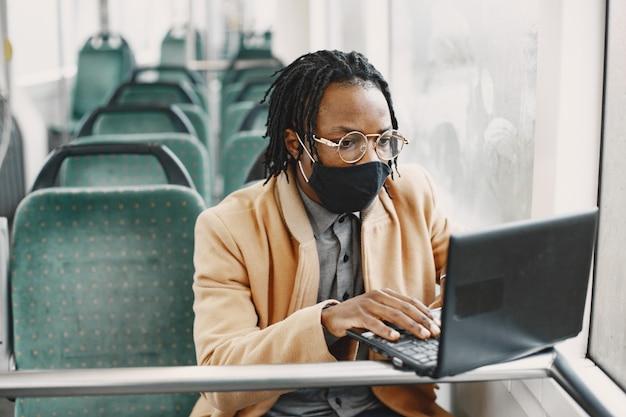 市バスに乗っているアフリカ系アメリカ人の男。茶色のコートを着た男。コロナウイルスの概念。