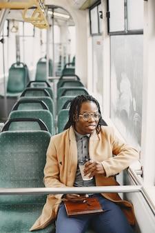 市バスに乗っているアフリカ系アメリカ人の男。茶色のコートを着た男。コーヒーを持つ男。