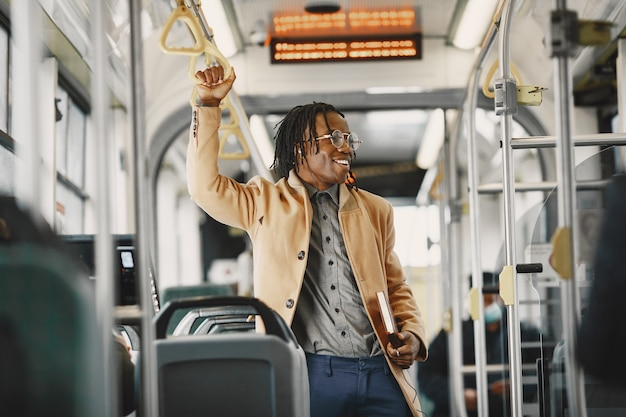 도시 버스를 타고 아프리카 계 미국인 남자입니다. 갈색 코트를 입은 남자. 노트북을 가진 남자입니다.