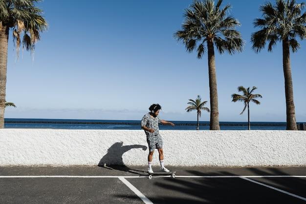 Афро-американский мужчина катается на лонгборде с пляжем на заднем плане - фокус на лице